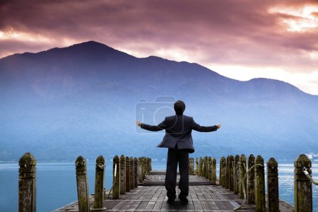 Businessman stand on the pier and watching the mountain and cloud of sunri