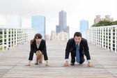 Business-Mann und Frau, die immer bereit für das Rennen in der Wirtschaft
