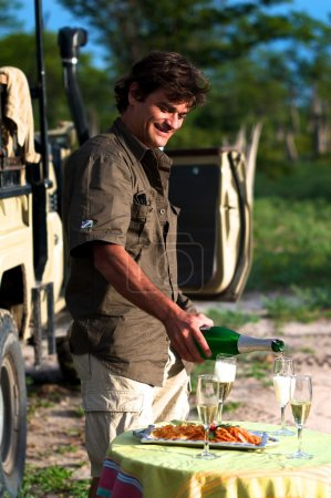 Man smiling and serving champagne