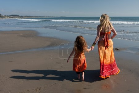 Photo for Beach stroll, mother and daughter holding hands and walking along ocean, facing away from camera. Colorful beach attire. - Royalty Free Image