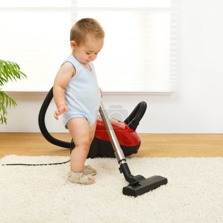 Baby boy cleaning the carpet with vacuum cleaner...