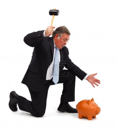 Photo for Serious business man raising hammer to break the piggy bank - Royalty Free Image