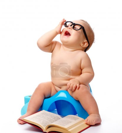 Photo for Child on potty play with glasses and book, isolated over white - Royalty Free Image