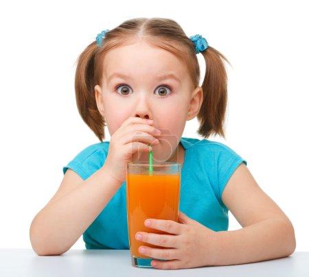 Foto de Niña linda bebe zumo de naranja con pajita y haciendo grandes ojos, aislado en blanco - Imagen libre de derechos