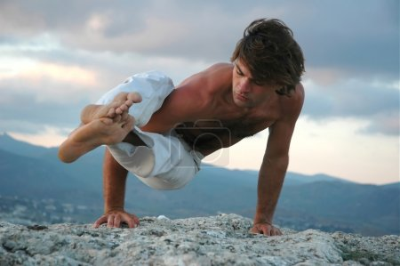 Photo for Young man doing an ashtavakrasana. Hand standing (variant) - Royalty Free Image