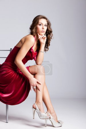 Photo for Young elegant woman in red dress sit on chair, studio shot - Royalty Free Image