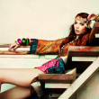 Young woman in colorfull summer clothes sit on sta...