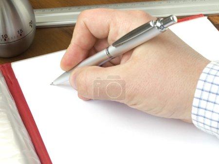 Hand hält einen Stift und ein Blatt Papier auf einem Schreibtisch