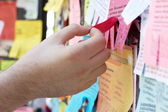Man hand tearing off advertising on bulletin board