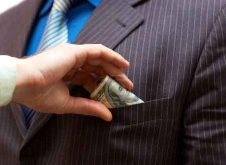 Man putting money into businessman side pocket