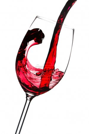 Red wine is poured into a glass. Closeup. Isolated on white back