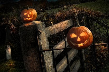 Two Halloween pumpkins sitting on fence