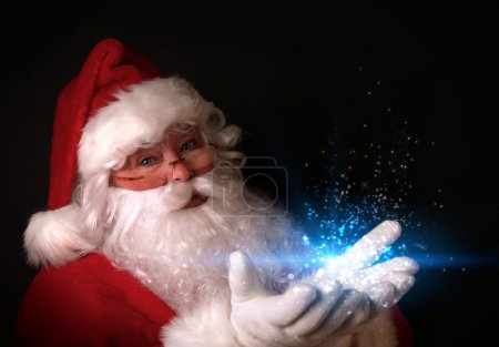 Photo for Christmas theme with Santa holding magical lights in hands - Royalty Free Image