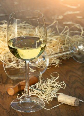 Glass of white wine with cork screw