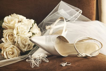 Photo for Wedding shoes with bouquet of white roses and ring on chair - Royalty Free Image