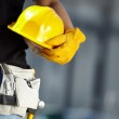 Builder with yellow helmet and working gloves on b...
