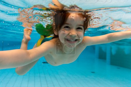 Photo for The little girl in the water park swimming underwater and smiling - Royalty Free Image