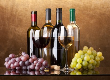 Photo for Several bottles of white and red wine, two glasses and grapes on a golden background - Royalty Free Image