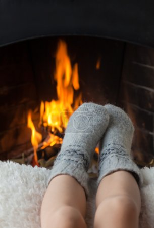 Children's feet are heated in the fireplace
