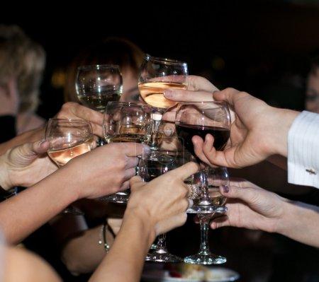 Photo pour Beaucoup de mains avec les verres de rouge et de vin blanc - image libre de droit