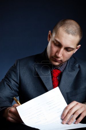 Photo for Businessman signing documents over blue background - Royalty Free Image