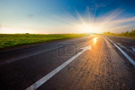 Photo for Black asphalt road with arrow to sunset - Royalty Free Image