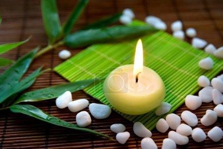 Photo pour Feuilles de composition avec bougie enflammée, de pierres blanches et de bambou, symbolisant le zen, de calme et de méditation - image libre de droit