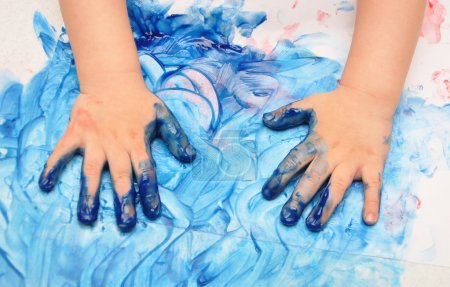 Photo for Child hands painted in blue paint ready for hand prints - Royalty Free Image