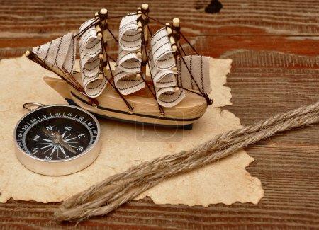 Photo pour Vieux papier, corde et modèle bateau classique sur fond de bois - image libre de droit