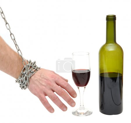 Photo for Chained hand reaches for the bottle - stop alcoholism concept - Royalty Free Image