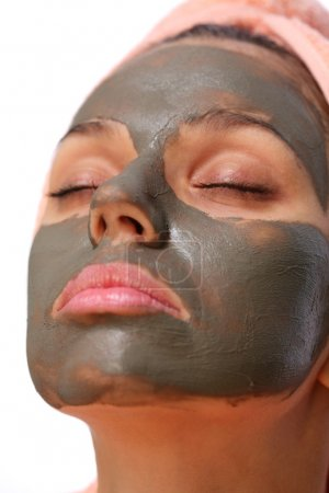 Face of young woman with mud mask on it.
