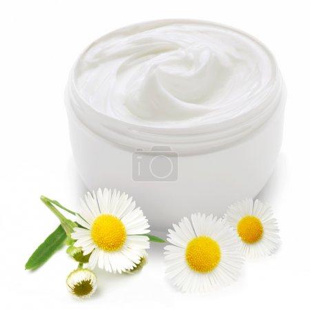 Photo pour Ouvert contenant de plastique avec la crème et de camomille sur un fond blanc. - image libre de droit