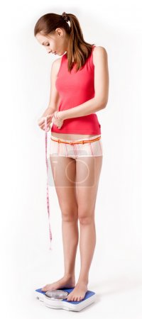 Girl on scales measuring her waist