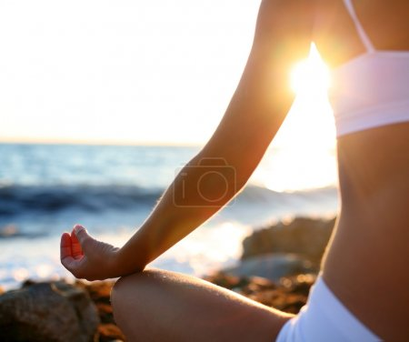 Photo for Body of a beautiful girl in a meditation on the beach - Royalty Free Image