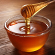 Honey pouring from drizzler into the bowl. Bowl is...