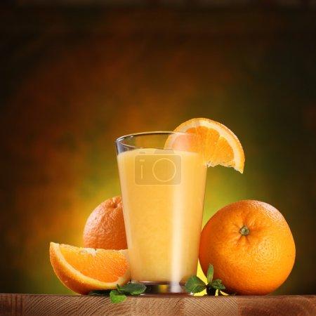 Photo pour Nature morte : oranges et verre de jus sur une table en bois. - image libre de droit