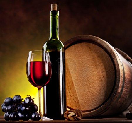 Photo pour Nature morte avec bouteille de vin, verre et fûts de chêne . - image libre de droit