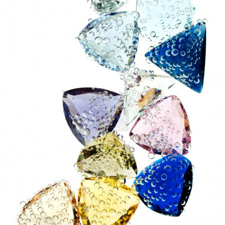 Multi-colored gems falling into water isolated on white.