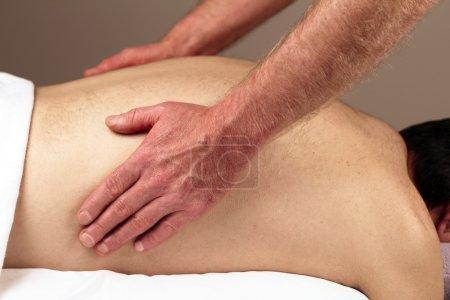 man massaging back sides