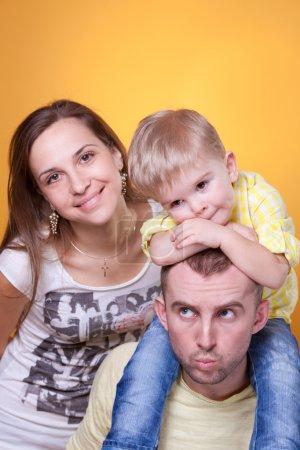 Photo pour Portrait de famille de jeunes parents avec petit fils sur les épaules du père - image libre de droit