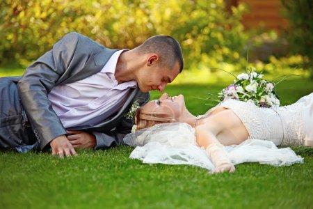 Photo pour Portrait de jeunes mariés heureux sur l'herbe dans le parc - image libre de droit