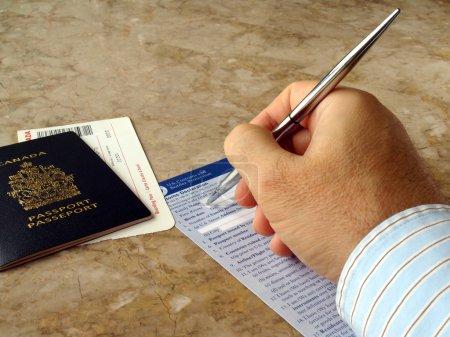 Photo pour Homme remplissant formulaire de douanes et de la frontière US avec passeport canadien - image libre de droit