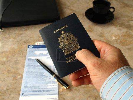 Photo pour Homme d'affaires, détenteurs d'un passeport canadien sur l'arrière-plan du formulaire de douanes et de la frontière américaine - image libre de droit