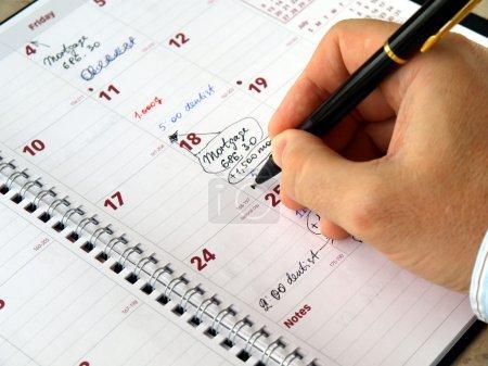 Photo pour Homme remplissant un planificateur mensuel sur la table - image libre de droit