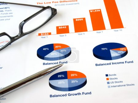 Photo pour Verres avec un stylo sur le graphique de l'investissement - image libre de droit
