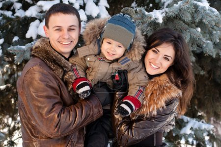 Photo for Attractive family having fun in a winter park - Royalty Free Image