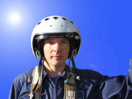 The military pilot in a helmet in dark blue overalls separately