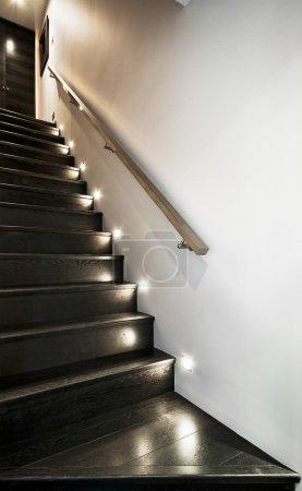 Photo pour Escalier en bois avec projecteurs et rail métallique - image libre de droit