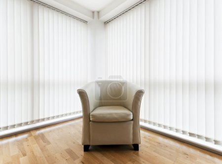 Photo for Beige leather armchair in a room with wooden floor and vertical blinds - Royalty Free Image