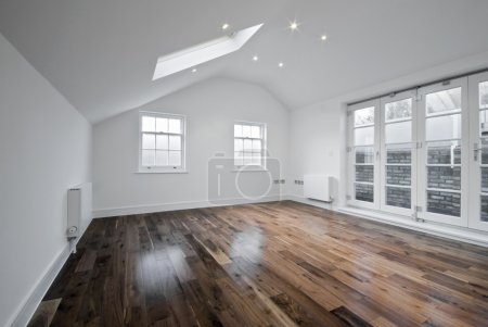 Photo for Empty unfurnished loft room with roof window and solid wood floor - Royalty Free Image